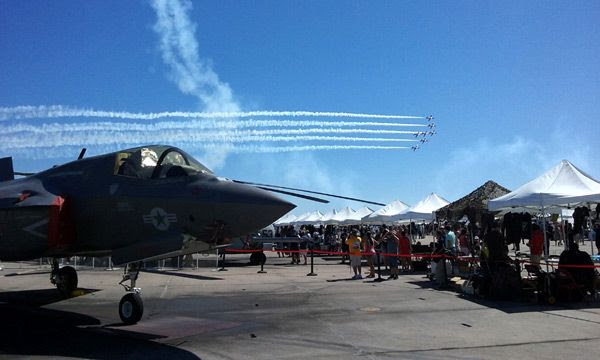 An air demo takes place behind the F-35B Lightning II parked on the tarmac at the Miramar Air Show...on September 24, 2016.