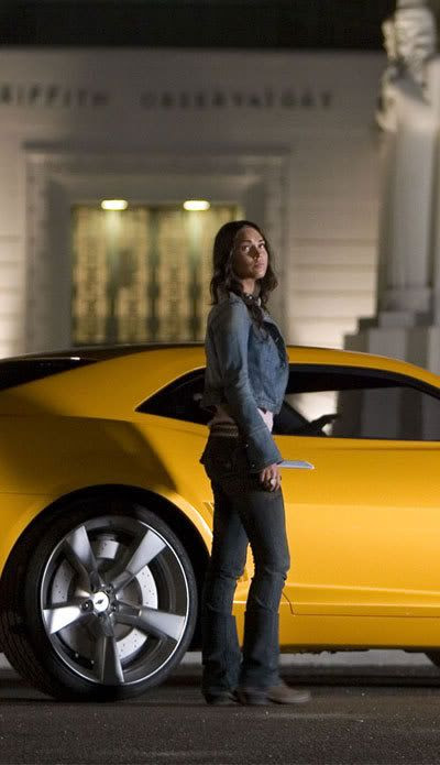 A production still of Megan Fox standing next to the 2009 Concept Camaro used for Bumblebee in TRANSFORMERS.