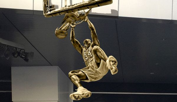 A composite image depicting Shaquille O'Neal's statue outside of STAPLES Center in downtown Los Angeles.