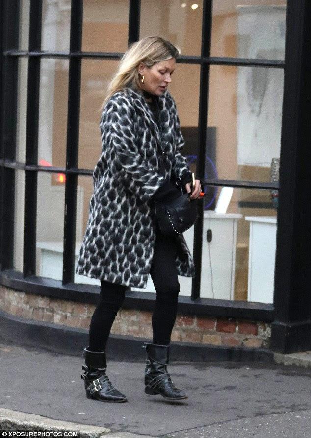 Manter quente: Ela usava um casaco preto e branco declaração com umas botas de tornozelo fivela para o passeio