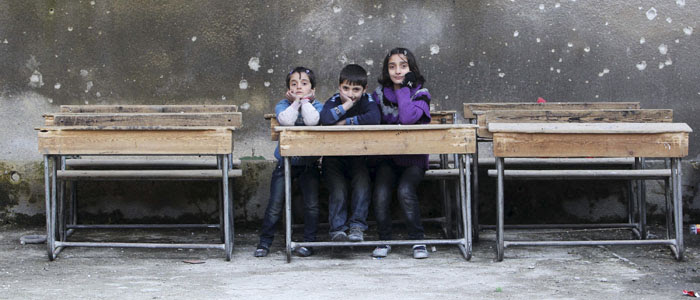 Children sit on school benches at Al-Tawheed school in Aleppo