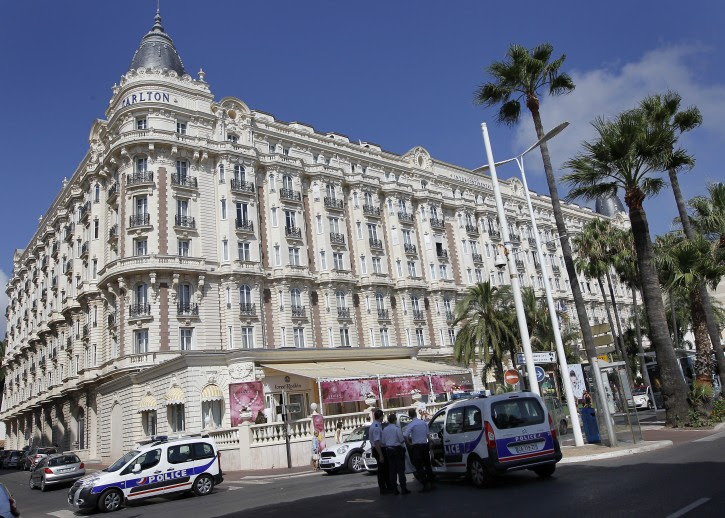 Police cars stand outside the Carlton Intercontinental Hotel in Cannes, southern France, 28 July 2013. EPA/SEBASTIEN NOGIER