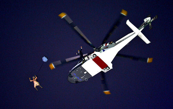 A performer in the role of Queen Elizabeth II parachutes out of a helicopter hovering above the Olympic Stadium during the opening ceremony on Friday.