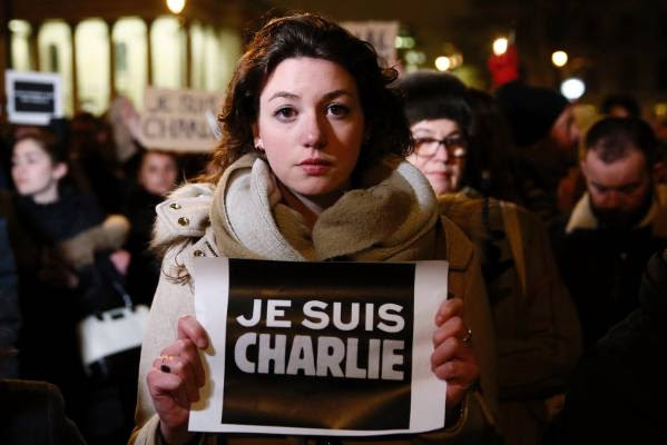 "A woman holds a placard that reads, ""I am Charlie"", during a vigil at Trafalgar Square in London."