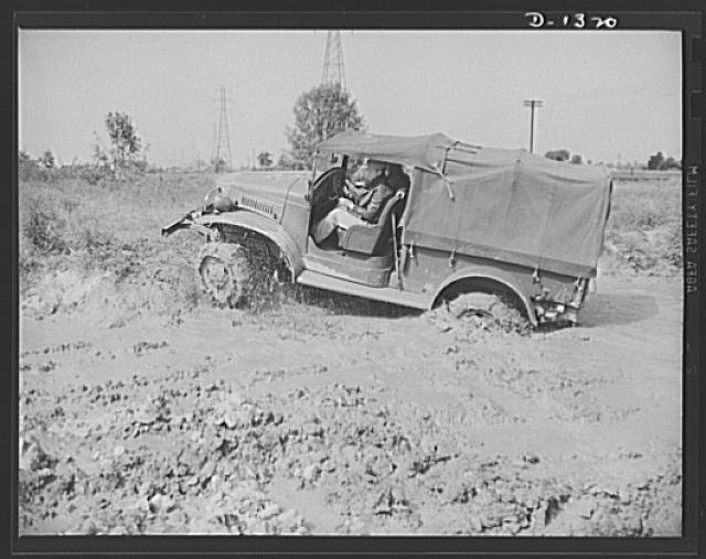 Army truck manufacture (Dodge). Army officers attending the school conducted by the Chrysler Corporation to assist our fighting forces in the job training men to operate the thousands of trucks required by today's streamlined division are given actual practice in driving the trucks in a testing field. Above is an Army officer putting one of these trucks through its paces in a heavy mud wallow which is just one of the many tests to which the driver and vehicle are subjected