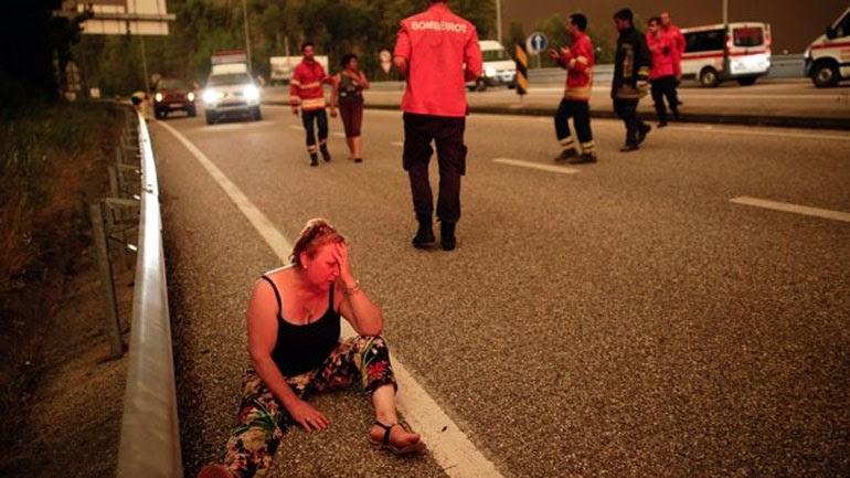 Μια γυναίκα κλαίει στην άκρη του δρόμου μη μπορώντας να συνειδητοποιήσει τι έχει συμβεί