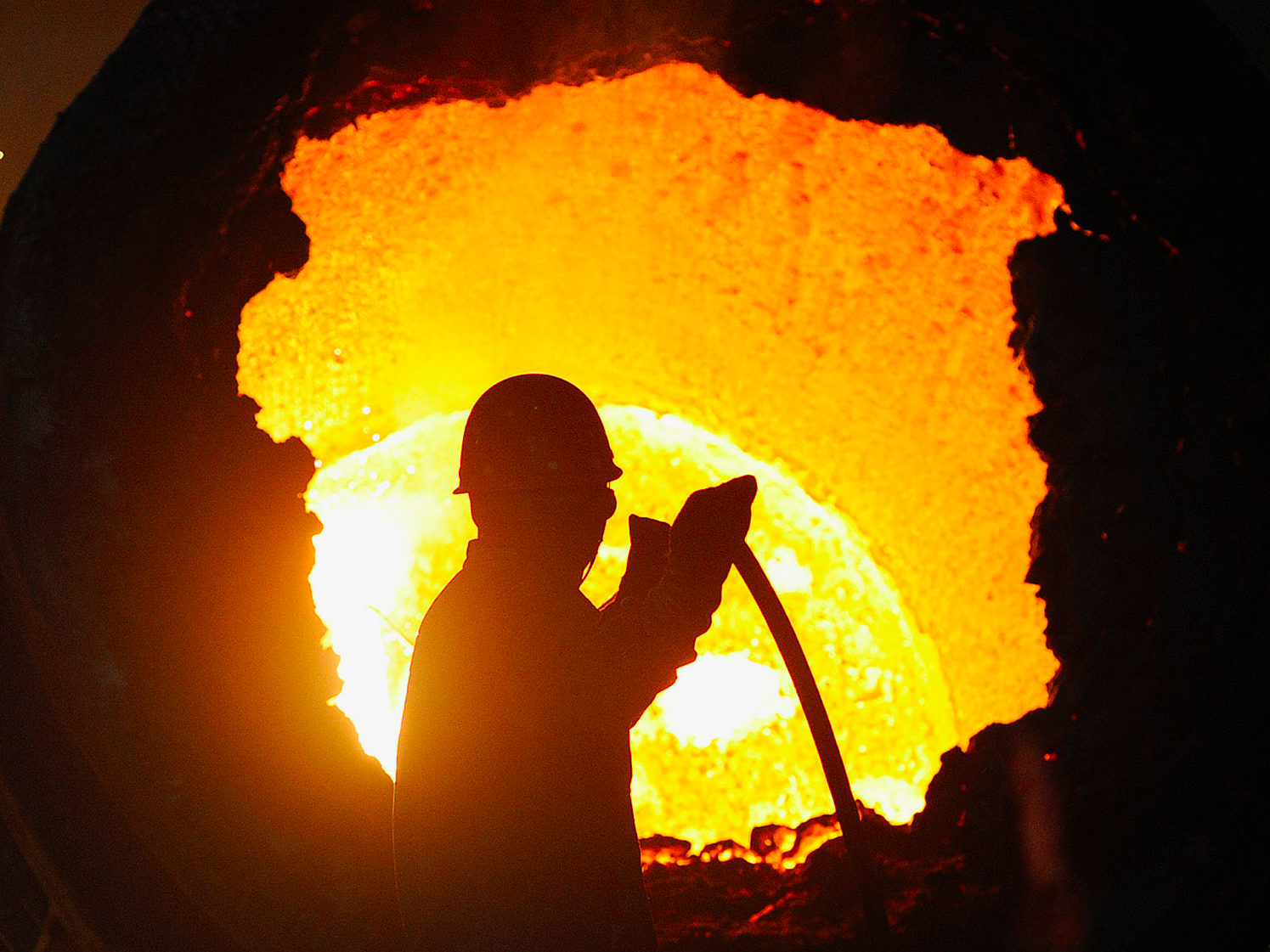 A worker operates a furnace at a steel plant in Hefei, Anhui province August 18, 2013. Momentum is growing in China to allow market forces to end a titanic capacity glut in heavy industry that a decade of state interventions has failed to resolve, according to speeches made by high-ranking officials this month at a closed-door event. The speeches indicate that China's reform-minded cabinet is considering a dose of deeper structural reform to remedy bloated, inefficient and debt-laden sectors such as steel.