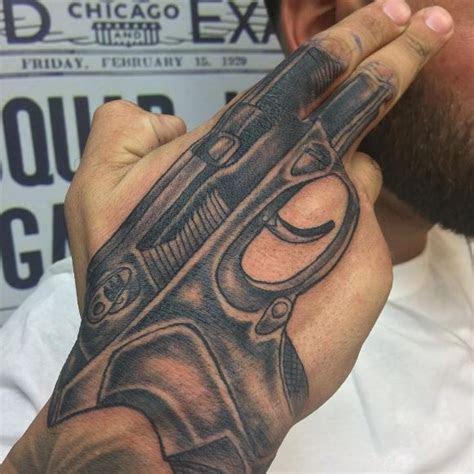 grey shaded gun tattoo upper hand