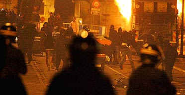 Rioters in front of a burning truck throw stones at the police in Villiers Le Bel, a northern suburb of Paris
