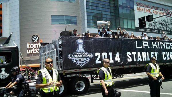 Los Angeles Kings center Anze Kopitar hoists up the Stanley Cup trophy as the flatbed truck carrying the 2014 National Hockey League (NHL) champions approaches STAPLES Center during their victory parade...on June 16, 2014.