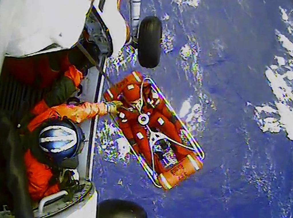 A frame from a video shows a crew member of the HMS Bounty being lifted to a Coast Guard rescue helicopter in a rescue basket, 90 miles southeast of Cape Hatteras, North Carolina. The Coast Guard rescued 14 people from life rafts after the ship went down in the rough seas of Hurricane Sandy.