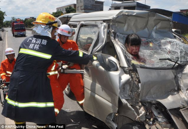 Rescue effort: Firefighters work to cut the woman free after the car she was traveling in crashed into the back of a lorry in China