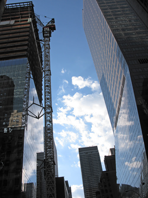 a midtown canyon with a crane and clouds, Manhattan, NYC
