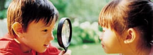 Kids looking at magnifying glass