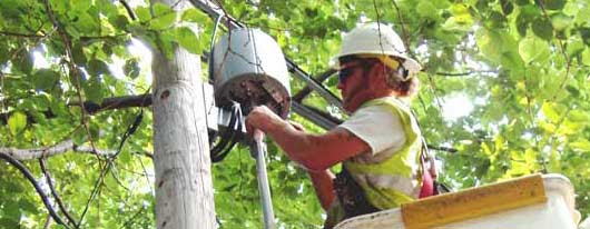 Photo of worker adjusting a wireless access point.