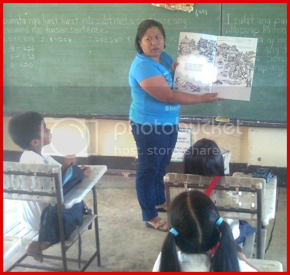 Kagawad Racquel D. Angelitud reading to the pupils