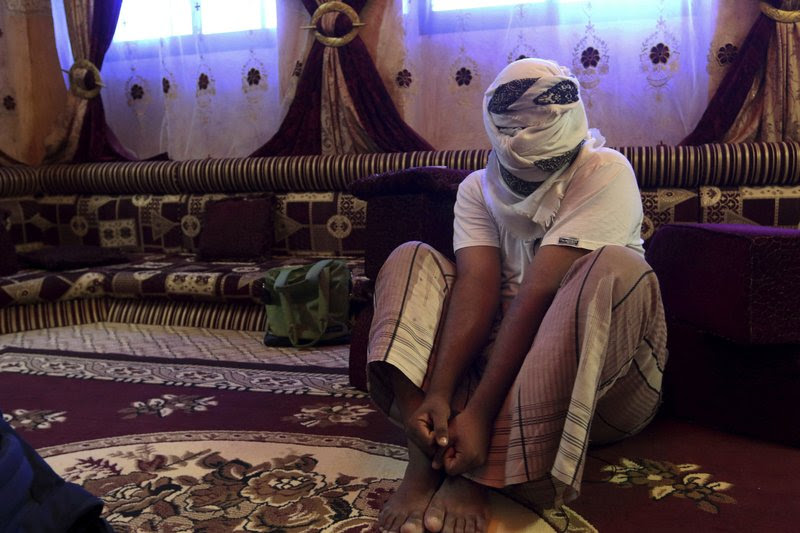 A former detainee shows how he was kept in handcuffs and leg shackles while held in a secret prison at Riyan airport in the Yemeni city of Mukalla in this May 11, 2017 photo. He covered his face for fear of being detained again. He and other former detainees say abuses are widespread in a network of secret prisons run by the United Arab Emirates and its Yemeni allies, into which hundreds detained in the hunt for al-Qaida militants have disappeared. (AP Photo/Maad El Zikry)