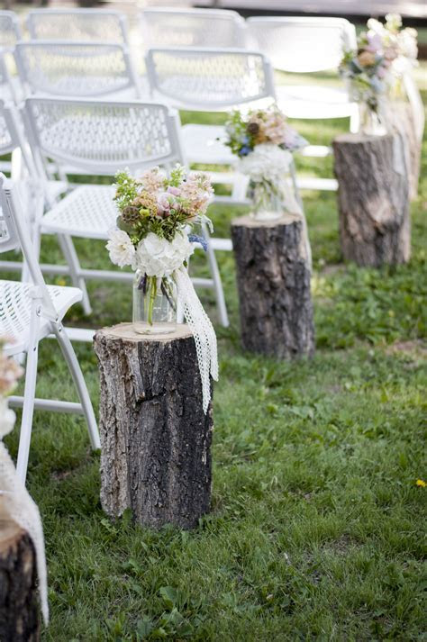 Aisle decor with wooden stumps, mason jars, lace, and