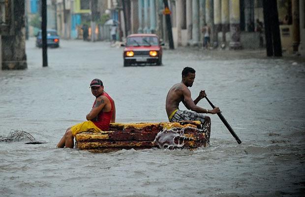 Homens usam barco improvisado para circular por rua inundada nesta quarta-feira (29) em Havana (Foto: Yamil Lage/AFP)