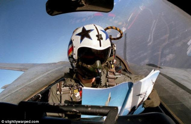 Taking a break: This pilot enjoys a magazine while seated in the back of a military fighter jet