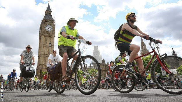 Lost of cyclists of all ages, cycling through London, Big Ben in the distance, behind them