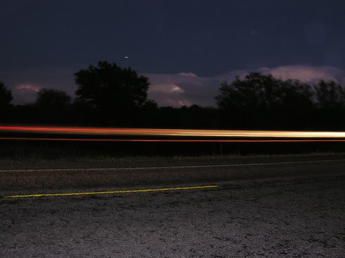 lightening lit up the skys and cars going by left light trails