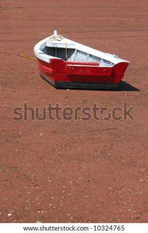 Small Red Wooden Row Boat On The Beach At Low Tide. Stock Photo
