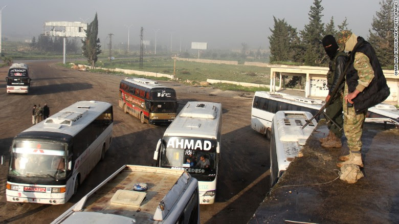 Opposition fighters monitor a bus convoy in Rashidin on Friday, the day before the bombing.