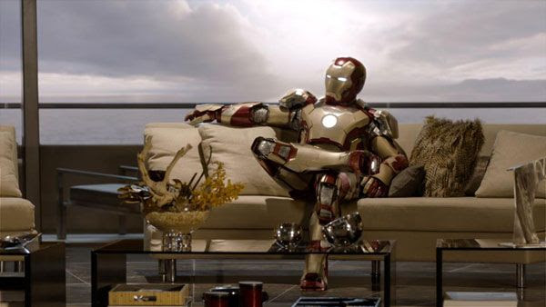 Still dressed in armor, Tony Stark (Robert Downey Jr.) kicks back on his couch in IRON MAN 3.