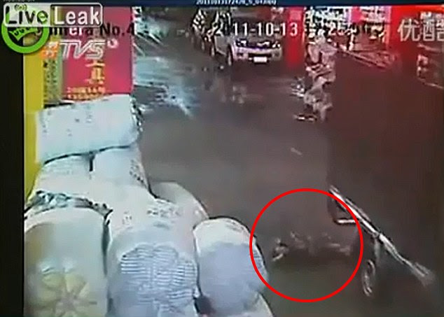 Horrific: Yue Yuem lies critically injured on the floor after she was run over by a van in Foshan city, Guangdong, China