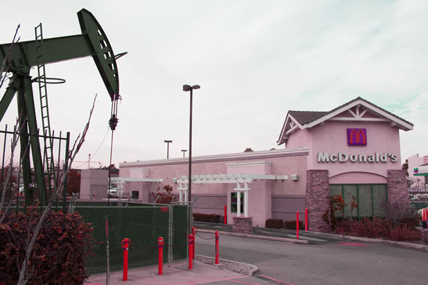 tinted photo of an oil pumpjack in the parking lot of a McDonalds restaurant