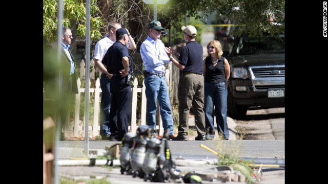 Law enforcement officers speak with Colorado Gov. John Hickenlooper, center, outside the suspect's apartment Saturday.