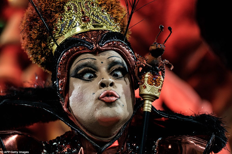 Wearing a jewel-coated crown and custom-made sceptre, another performer pulls a funny face as they dance through the stadium
