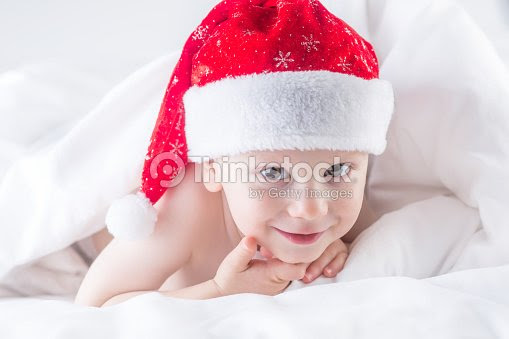 Cute Baby Boy With Santa Hat On Bed Under White Duvet Stock Photo