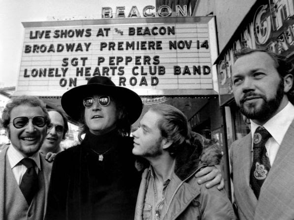 "Former Beatle John Lennon, center, poses in front of the marquee at New York's Beacon Theater on Thursday, Oct. 17, 1974 where the ""Sgt. Pepper's Lonely Hearts Club Band on the Road"" will open soon. Lennon has his arm around Bruce Scott, who will perform in the musical."