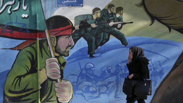 An Iranian woman walks past a mural in Tehran, 16 January
