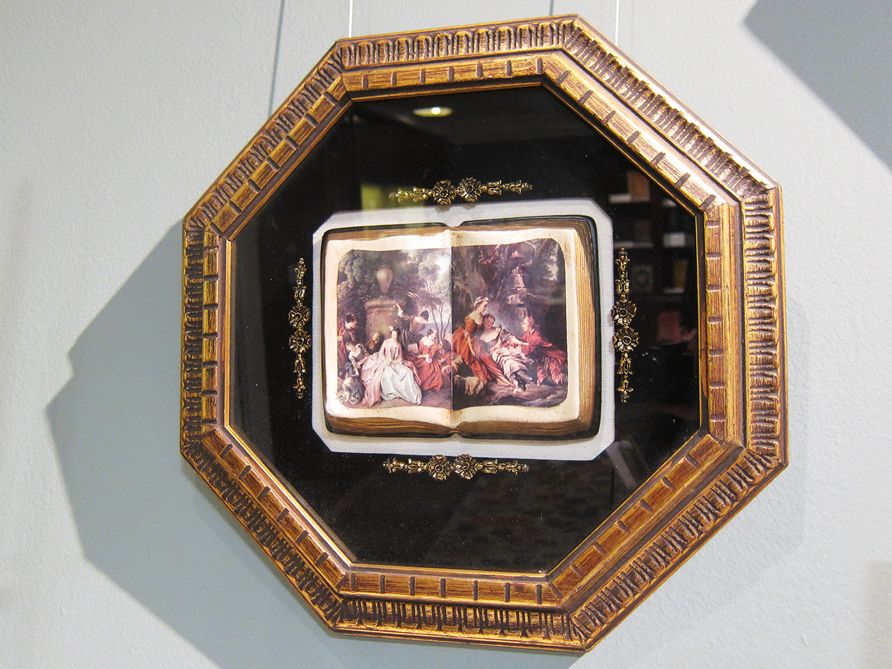 A framed faux box with three-dimensional open books showing decoupage images of famosu European paintings (mid-20th c.)