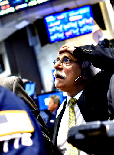 A trader gestures on the floor of the New York Stock Exchange at the start of the trading day in New York, New York, USA,on Monday. Global markets have been reacting to the economic situation in China and the Dow Jones Industrial average followed that trend losing 1,000 points in early trading