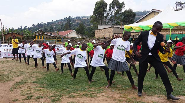 Isaac performing with happy children at Kabale School, Uganda