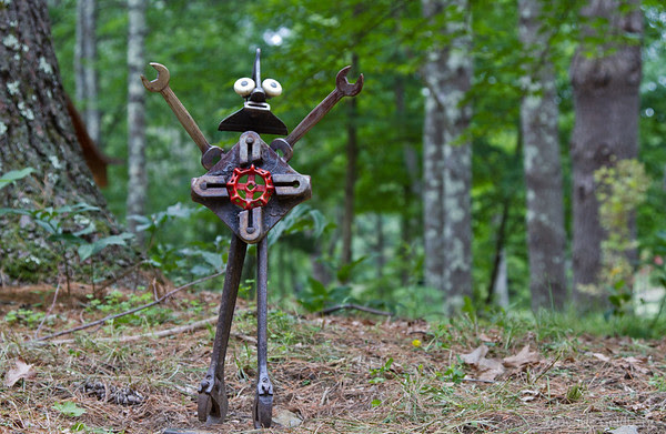 Bedrock Gardens sculpture standing in a clearing (in the woods)