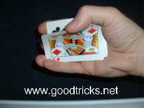 Grip end of pack with fingers and pull off top card with thumb.