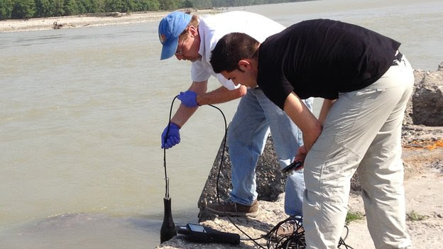 Professor Graham and a colleague takes a water sample from the River Ganges
