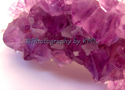 a macro shot of purple amethyst crystals