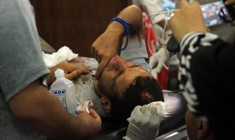 Seorang pria pendukung Presiden Mursi yang terluka akibat ditembak tentara, tengah dirawat di Kairo, Mesir, Senin (8/7). (AP/Ahmed Gomaa)
