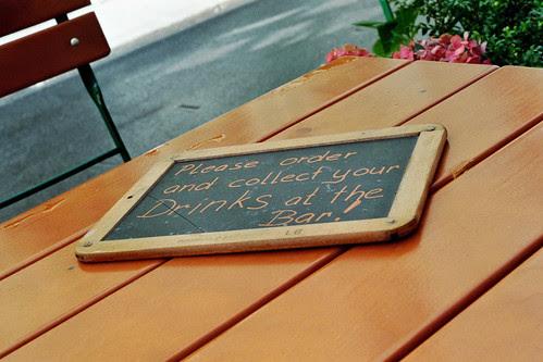 Photo handgeschriebenes Schild 'Collect your drinks at the bar' auf Holztisch