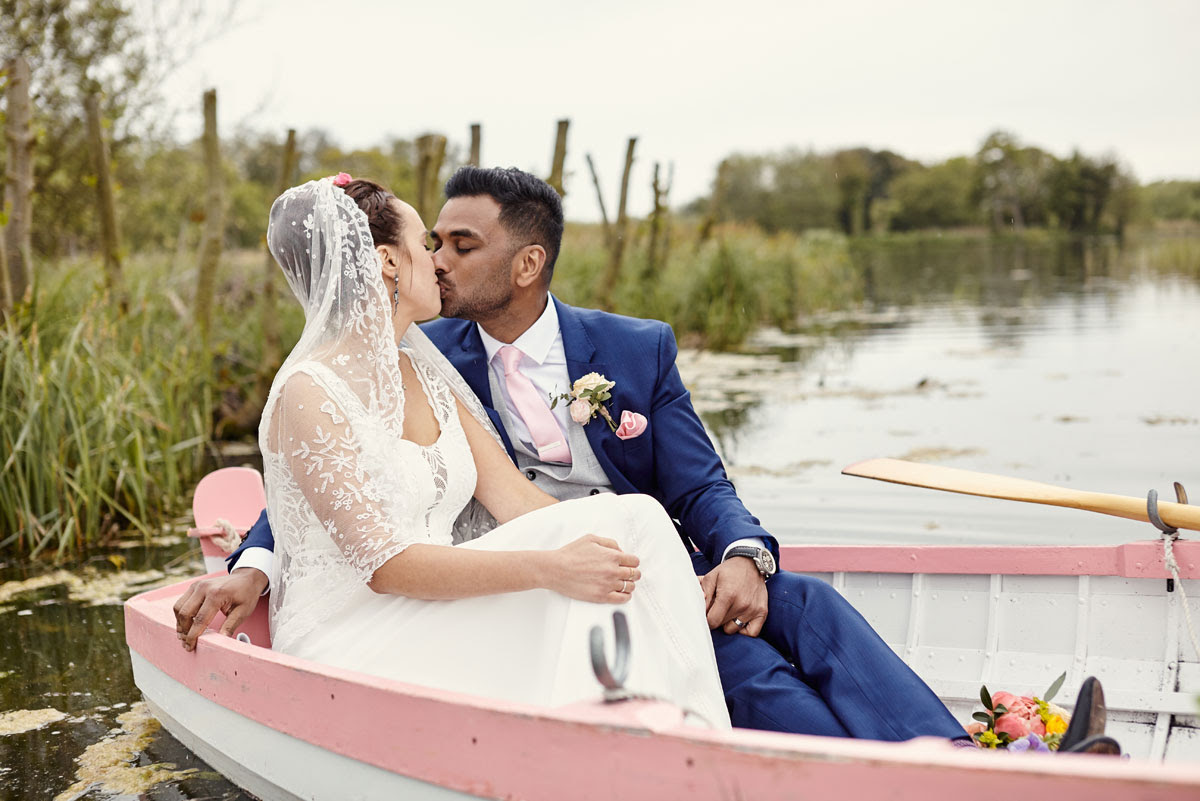 Bride and Groom in rowing boat at Thorpeness Meare Wedding Photo - helloromancephotography.com