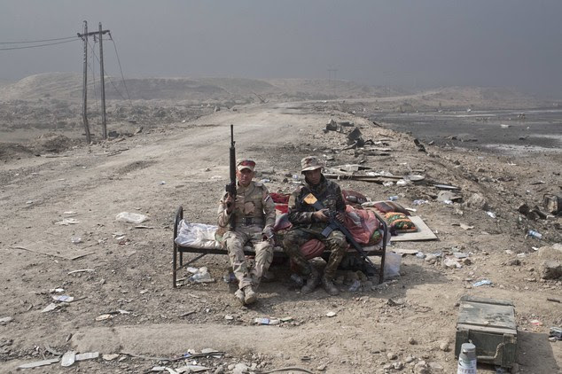 Iraqi army soldiers rest at a checkpoint in Qayara some 50 kilometers south of Mosul Iraq Wednesday Oct. 26 2016. Islamic State militants have been goin
