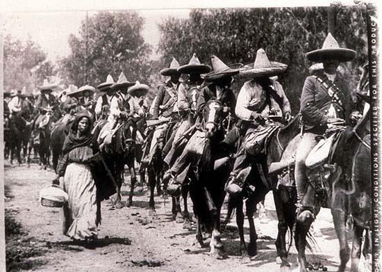 Mexico, Revolution. Gyalogló nő a lovagló zapatisták oszlopa mellett. Agustín Victor Casasola (1874-1938) fotója. Vö. http://content.cdlib.org/ark:/13030/hb1p300718/?layout=metadata&brand=calisphere