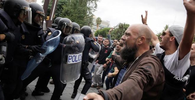 Agentes de la Policía Nacional fretne a las personas concentradas en un colegio electoral en Tarragona, durante la jornada del referéndum del 1-O. REUTERS/David Gonzalez