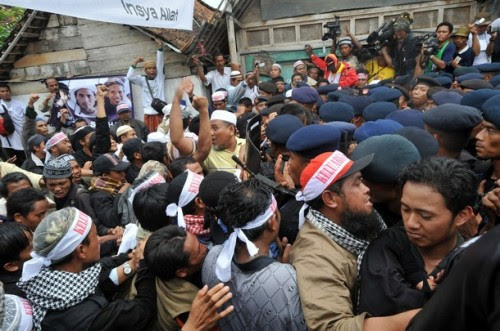 """Indonesian Mobile Brigade Policemen clash with supporters shortly before the funeral of the bodies of Amrozi and Mukhlas in Tenggulun on November 9, 2008. Grief and religious fervour boiled over into calls for revenge here as two brothers executed for their role in the 2002 Bali attacks were buried amid tight security.   A crowd of about 500 supporters briefly clashed with police near the family home of 47-year-old Amrozi -- dubbed the """"smiling assassin"""" for his disturbing grin -- and Mukhlas, 48, as their bodies arrived in their east Java village. AFP PHOTO/ADEK BERRY (Photo credit should read ADEK BERRY/AFP/Getty Images)"""